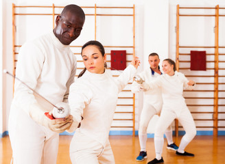 fencer practicing  movements with african american trainer