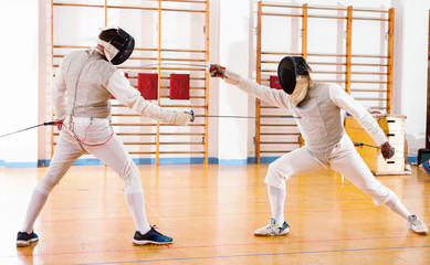 Portrait of athletes at fencing workout, practicing attack movements in duel