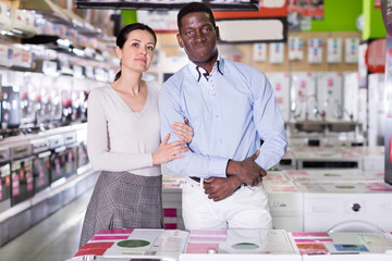 Couple standing in store of household appliances