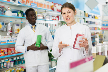 two pharmacists offering medication