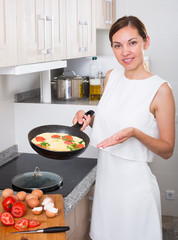 woman preparing omelet in pan