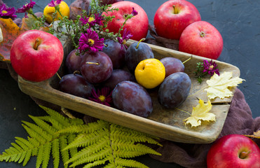 fresh fruits and vegetables with flowers on the wooden plate
