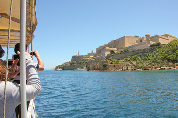 Tourists on boat travel on Grand Harbour taking photo of the most famous view of Valletta, Malta