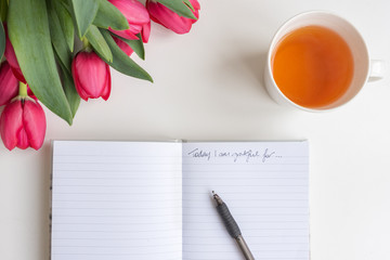 "Close up high angle view of red tulips, cup of tea and journal with pen and handwritten ""Today I am grateful for"""