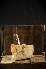 Parmesan cheese with knife on wooden board on dark background