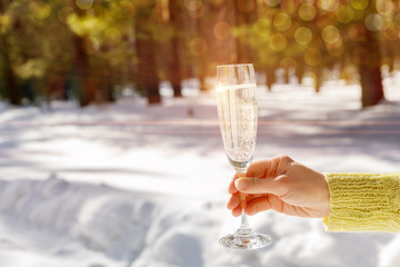 A hand holding a glass of fizzing champagne against the snowy winter background.