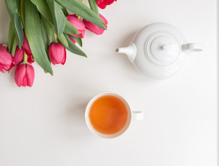 Top view of cup of tea, white teapot and red tulips with green leaves on white background