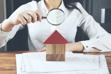 woman hand house model with magnifier