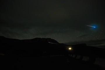 A bright meteorite in the night sky with clouds and stars in the North Caucasus in Russia.