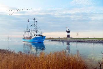 Krabbenkutter kommt zurück in den Heimathafen, Kutterhafen in Wremen mit Leuchtturm an der Wurster Nordseeküste