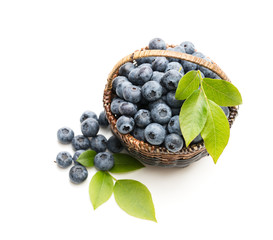 Fresh blueberries in small wicker basket isolated on white
