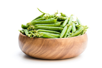 Fresh green pea pods in wooden bowl isolated on white