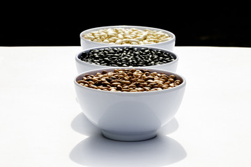 varieties of beans in bowls, white background