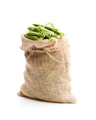 Fresh green pea pods in sack bag isolated on white