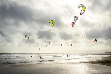 un ciel gris au dessus d'une plage en contre jour avec des voiles  de kitesurf