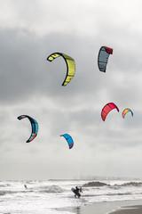 six voiles de kitesurf colorées en contre jour sous un ciel gris