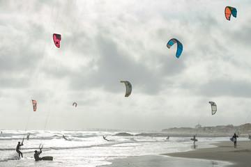 des kitesurf sur une plage en contre jour