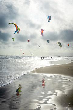 des voiles de kitesurf et leurs reflets sur l'eau de la plage