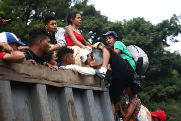 A Honduran migrant, part of a caravan trying to reach the U.S., climbs on a truck during a new leg of his travel in Zacapa