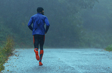 Motivated young man running in the rain. Rear view. Copy space.