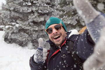 Young man taking selfie on snowy day and showing thumb up.