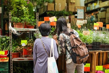 Hong Kong - April , 2018: flower market in Kowloon, Hong Kong, two Asian Women picks flowers for home interior