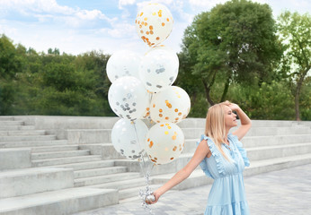 Beautiful young woman with bunch of balloons outdoors