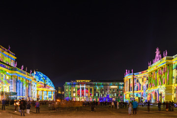 Night atmosphere of people enjoy event Festival of Lights, Berlin Leuchtet, the projection mapping lighting art on opera, Cathedral buildings around Bebelplatz.