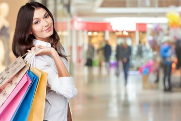 Young woman with shopping bags on blurred