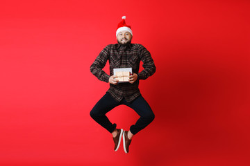 Smiling guy jumping with Christmas presents
