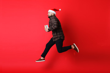 Young guy leaping with Christmas gifts