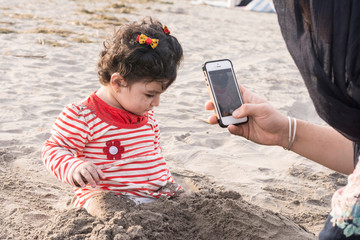 Little kid playing at beach with sand and her mother taking photos by smartphone