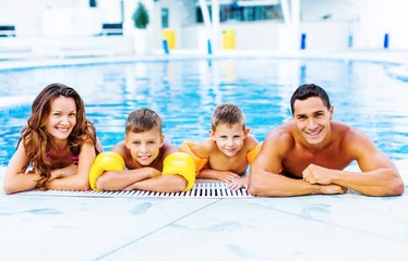 Happy family playing in swimming pool. Summer