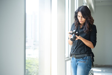 young hipster woman photographer  holding camera near the window.