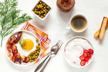 Breakfast - fried eggs with bacon and green peas, coffee and cottage cheese with strawberry on a light background. Selective focus. Top view. Flat lay