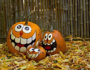 A Hand Painted Jack-O-Lantern Family Against Weathered Bamboo