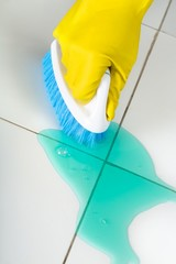 Hand in Rubber Glove Holding a Brush and Cleaning Tiles