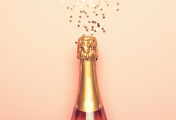 Christmas or New Year pink background with  bottle of sparkling wine, rose champagne and gold decor, top view