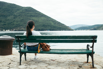 woman sitting at bench with beautiful view of sea and mountains