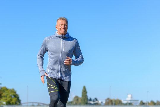 Gray smiling man running through a park
