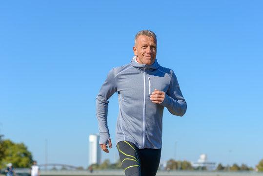 Gray smiling man running along river