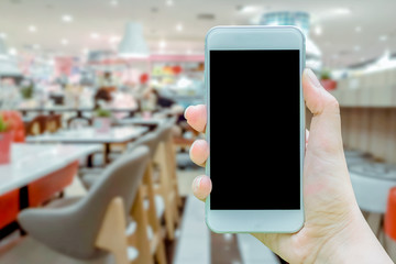 Mockup image of hand holding white cellphone with blank black screen that taking pictures cafe is in shopping mall is blurred on background.