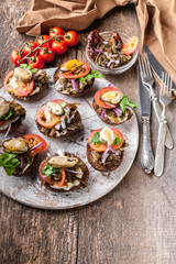 Canapes with cream cheese and tomatoes on a round chopping board. Mediterranean Kitchen. Vertical shot