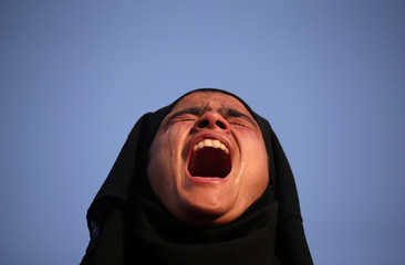 A girl cries as she watches the body of Mehraj-ud-Din Bangroo, a suspected militant, who according to local media was killed in a gunbattle with Indian security forces, during his funeral procession in Srinagar