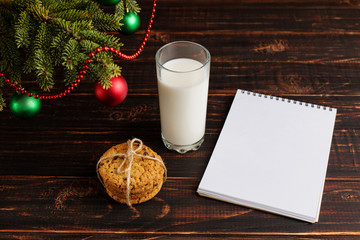 Milk, cookies and a wish list under the Christmas tree. The concept of the arrival of Santa Claus.