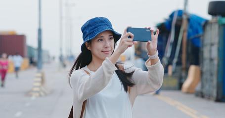 Tourist woman take photo on cellphone in Hong Kong landmark