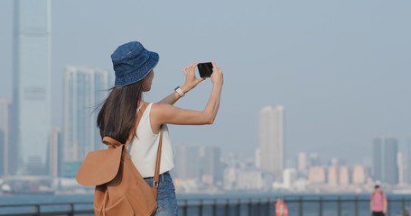 Woman take photo on cellphone in Hong Kong