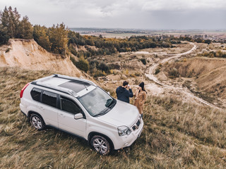 couple standing near suv car at the cliff with beautiful view from the top.