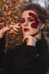 Beautiful young girl with applique red roses flowers on the face in nature autumn