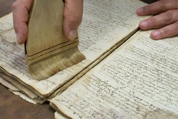 Obraz Restoration laboratory. Dusting old book conservation - fototapety do salonu